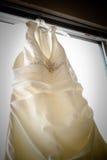 Hochzeits-Kleid, das im Fenster hängt Lizenzfreie Stockbilder
