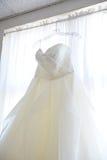 Hochzeits-Kleid, das oben im Fenster hängt Lizenzfreie Stockfotografie