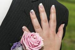 Hochzeits-Knopf des Bräutigams und der Hand der Braut Lizenzfreie Stockfotos