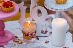 Hochzeits- oder Parteischokoriegel, verzierte Nachtischtabelle in der rosa Farbe mit Kuchen Schäbige schicke Art Lizenzfreie Stockfotografie