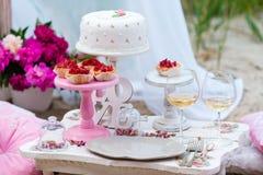 Hochzeits- oder Parteischokoriegel, verzierte Nachtischtabelle in der rosa Farbe mit Kuchen Schäbige schicke Art Lizenzfreie Stockfotos