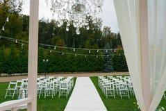 Hochzeits-Ort Weiße Stühle auf grünem Gras mit Nacht beleuchtet Hochzeitseinrichtung Hochzeitseinstellung Stockbilder