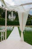 Hochzeits-Ort Weiße Stühle auf grünem Gras mit Nacht beleuchtet Hochzeitseinrichtung Hochzeitseinstellung Porträtfoto eintragfade Stockfotografie