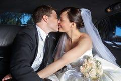 Hochzeits-Paar-Kuss in der Limousine Lizenzfreies Stockfoto