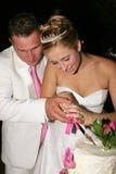 Hochzeits-Paare, die den Kuchen schneiden Stockbild