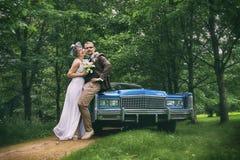 Hochzeits-Paare nahe dem Brautauto Stockfotografie