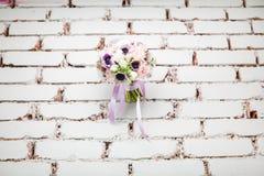 Hochzeits-Pfingstrosen-Blumenstrauß auf Backsteinmauer-Hintergrund lizenzfreie stockbilder