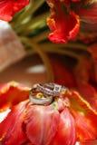 Hochzeits-Ringe auf Blumenstrauß Stockfotografie