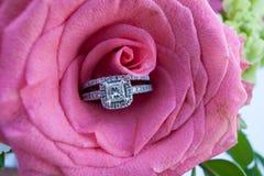 Hochzeits-Ringe in einer rosafarbenen Rose Stockfoto