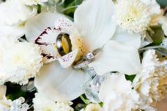 Hochzeits-Ringe u. Blumen Stockbilder