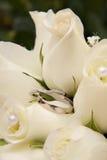 Hochzeits-Ringe und weiße Rosen Lizenzfreies Stockbild