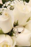 Hochzeits-Ringe und weiße Rosen Stockbilder
