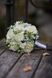 Hochzeits-Ringe und weißer Rosen-Blumenstrauß Lizenzfreies Stockfoto