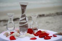 Hochzeits-Sandzeremonie mit den Blumenblättern und den Oberteilen Stockfoto