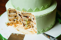 Hochzeits-Torte mit geschnittenem Stück und Messer nahe Tischbesteck lizenzfreie stockbilder