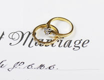 Hochzeits- und DiamantVerlobungsringe auf Heiratsurkunde Stockbilder