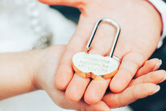 Hochzeits-Verschluss als Symbol der Heirat in den Händen der Braut und des Bräutigams Lizenzfreies Stockfoto