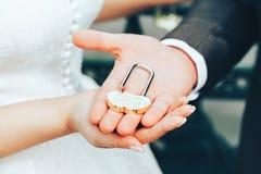 Hochzeits-Verschluss als Symbol der Heirat in den Händen der Braut und des Bräutigams Stockfoto