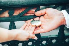 Hochzeits-Verschluss als Symbol der Heirat in den Händen der Braut und des Bräutigams Stockfotografie
