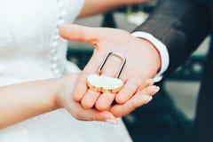 Hochzeits-Verschluss in den Händen der Braut und des Bräutigams Lizenzfreie Stockbilder