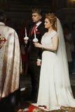 Hochzeits-Zeremonie an der Kirche stilvoller Bräutigam und Braut, die cand hält stockfoto