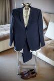 Hochzeitsanzug, Hemd, Hose, Schuhe des Bräutigams hängend am Aufhänger stockfotografie