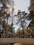 Hochzeitsaufschrift mit großen weißen Buchstaben auf einem Hintergrund des grünen Parks stockfotos