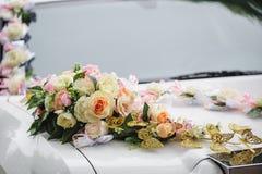 Hochzeitsautodekoration von Blumen mit Rosen und Schmetterlingen Lizenzfreies Stockbild