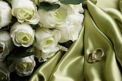 Hochzeitsbänder auf grünem Satin Lizenzfreies Stockfoto