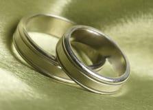 Hochzeitsbänder schließen oben auf grünem Satin Stockfotografie