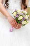 Hochzeitsbündel blüht in den Händen der Braut Stockfotografie