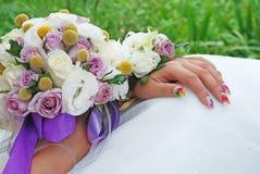 Hochzeitsblumen in den Händen der Braut Stockbilder