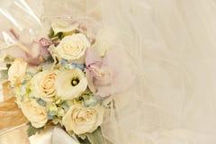 Hochzeitsblumen und Elfenbeinbrautschleier Stockfotos
