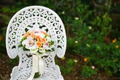 Hochzeitsblumenblumenstrauß auf einem weißen Gartenstuhl Stockbild