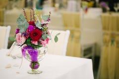 Hochzeitsblumenblumenstrauß im Glasvase auf Gasttabelle Stockfotografie