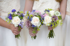 Hochzeitsblumensträuße angehalten von den Brautjunfern lizenzfreie stockbilder