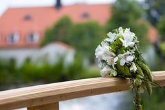 Hochzeitsblumenstrauß auf Brücke stockfotografie