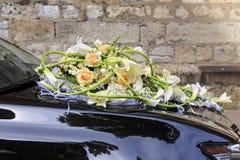 Hochzeitsblumenstrauß auf dem schwarzen Auto stockbild