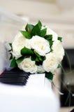 Hochzeitsblumenstrauß auf einem weißen Klavier Stockfoto