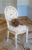 Hochzeitsblumenstrauß auf einem weißen Stuhl schön Lizenzfreie Stockfotos