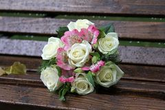 Hochzeitsblumenstrauß auf einer Holzbank im Park lizenzfreie stockbilder