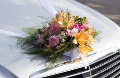 Hochzeitsblumenstrauß auf einer vorderen Haube eines Autos Stockfotos