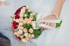 Hochzeitsblumenstrauß auf Hochzeitskleid Stockbild