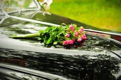 Hochzeitsblumenstrauß auf Verkleidung des schwarzen Autos Stockfotos