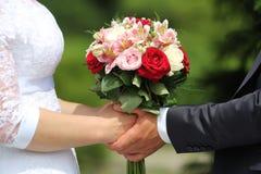 Hochzeitsblumenstrauß in den Braut- und Bräutigamhänden Stockfotografie