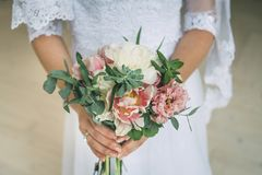 Hochzeitsblumenstrauß in den Brauthänden lizenzfreie stockbilder