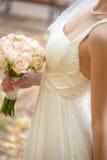Hochzeitsblumenstrauß an den Händen der Braut Stockfotografie