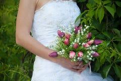 Hochzeitsblumenstrauß an den Händen der Braut Stockfotos