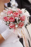 Hochzeitsblumenstrauß in den Händen der Braut in einem weißen Kleid Stockfoto