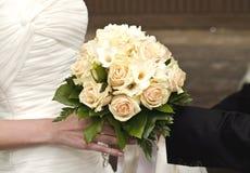 Hochzeitsblumenstrauß in den Händen der Braut und des Bräutigams Lizenzfreie Stockfotos